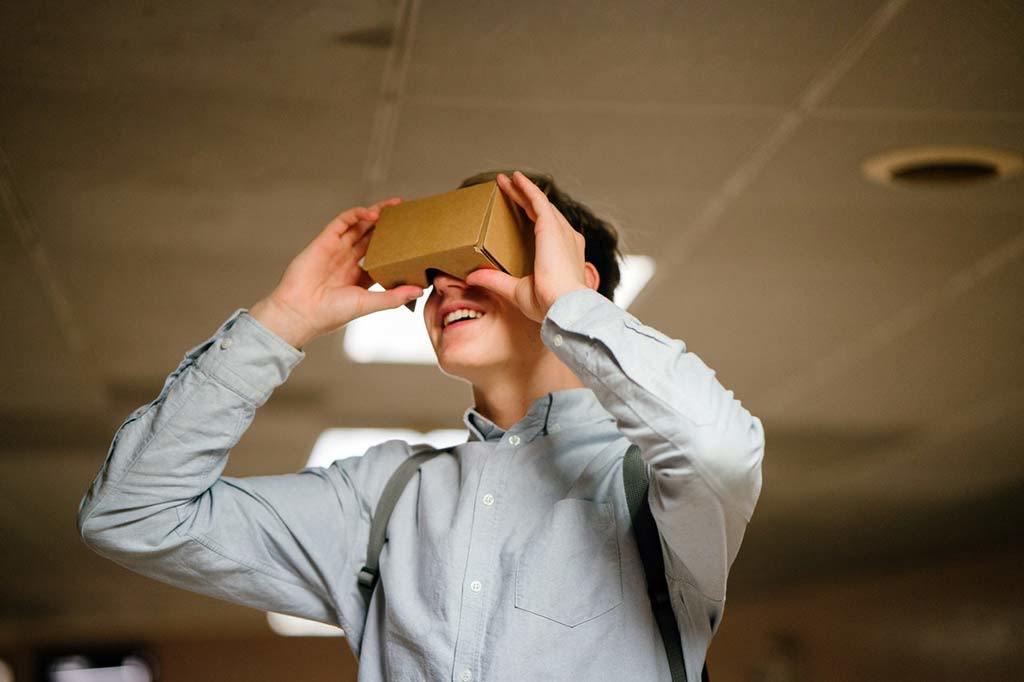 Man in grey dress shirt using brown cardboard vr glasses 936575 1
